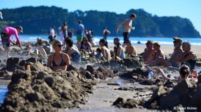 Hunderte von Menschen graben sich an der selben Stelle ein Loch im Sand, um darin wie in der Badewanne zu sitzen… @ Hot Water Beach.