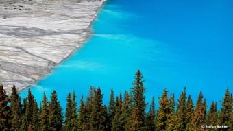 Schmelzwasser befördert Unmengen von Gesteinsmehl in den See. Mikroskopisch feine Schwebeteile erzeugen durch Reflexion des blaugrünen Bereiches des Lichtspektrums die türkise Färbung.